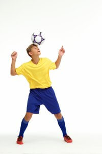 サッカーのヘディングをする子供